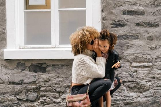 sai-de-silva-41030-unsplash+mom+whispering+daughter+outside+stone+house (1)