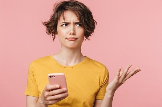 confused beautiful woman with pink background and cell phone.jpg