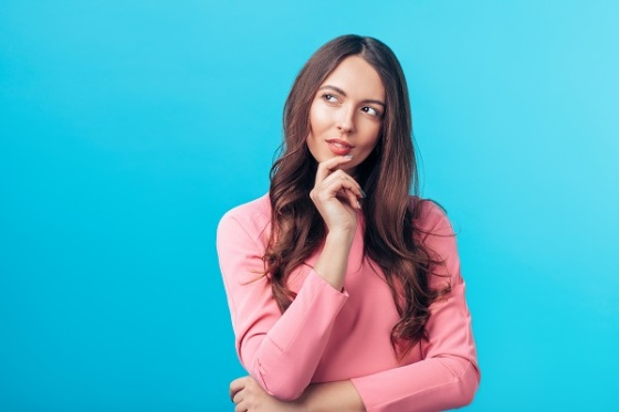 Portrait of thoughtful wondering woman looking sideways isolated over blue background