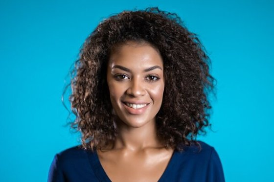 Attractove african american woman with afro hair in business clothing smiling to camera over blue wall background.jpg